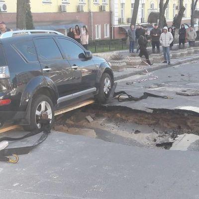В Киеве от прорыва трубы провалился асфальт с припаркованным внедорожником (фото)