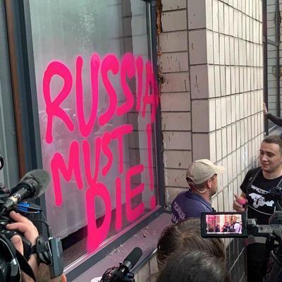 Люди под окнами здания телеканала NewsOne принесли с собой баллоны с краской, чтобы разрисовать здание